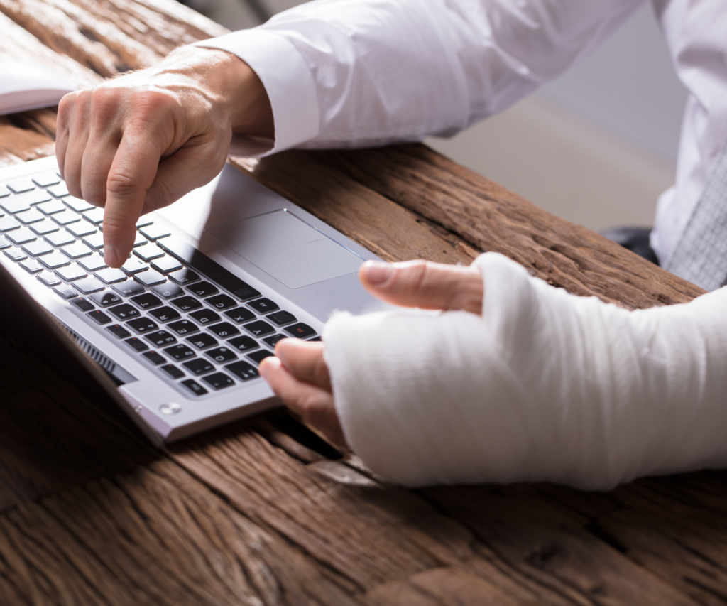 person with a cast using a laptop